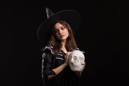 Portrait of little girl dosing dark sorcery with a human skull at halloween carnival. Little girl dressed up like a witch for halloween. Stock Photo