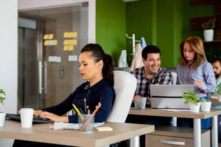 Busy day in start-up company office. Employees are working at their desk Stock Photo