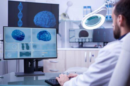 Giovane assistente medico che lavora al computer in un laboratorio ospedaliero. Diagnosi del cervello. Archivio Fotografico