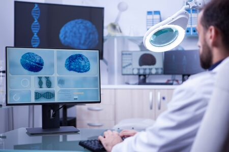 Young medical assistant working on computer in a hospital laboratory. Brain diagnosis. Stock Photo