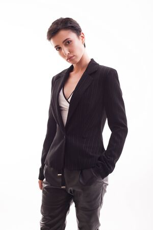 Confident young fashion model wearing black jacket and pants over white background in the studio. Fashion attitude.