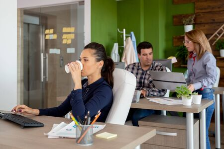 Gorgeous businesswoman drinking coffee in busy start-up company office