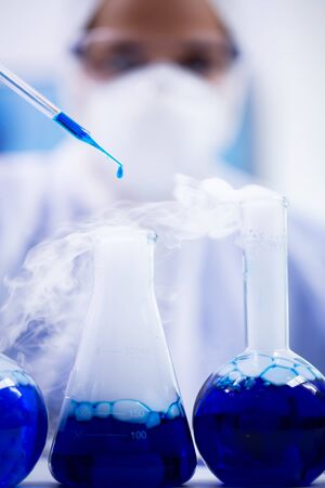 Close up of blue solution dropping from pipette in a test tube with smoking liquid. Scientist in protection equipment.