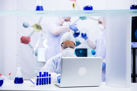 Chemist stands in front of the laptop with some test tubes next to him and two colleagues discuss in the back 写真素材