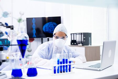 The female chemist looks at a tube holder with a blue liquid