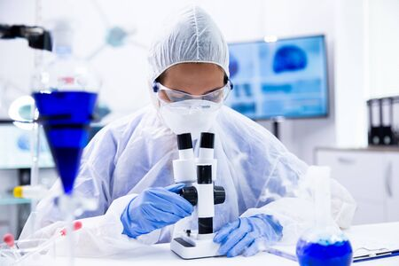 Chemist with safety glasses looks in the microscope and adjusts it Stockfoto
