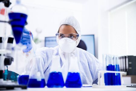 Female scientist in coverall equipment looking at a sample