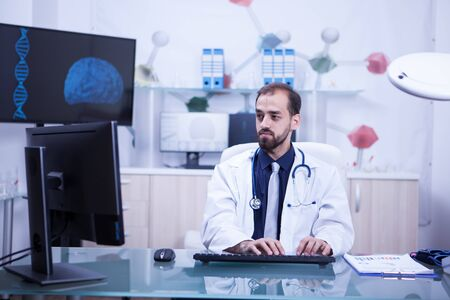 Young handsome doctor working and typing in his cabinet Stockfoto