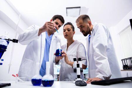 Zespół naukowców w białym fartuchu przeprowadza burzę mózgów. Nowoczesne laboratorium Zdjęcie Seryjne