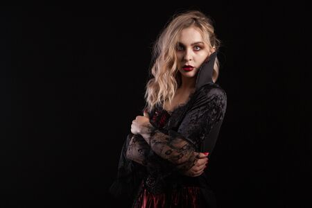Side view portrait of beautiful blonde woman dressed up like a vampire for halloween carnival. Stylish vampire woman.