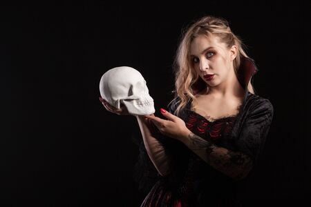 Sexy vampire woman holding skull and looking at the camera for halloween isolated on dark background. Halloween costume.