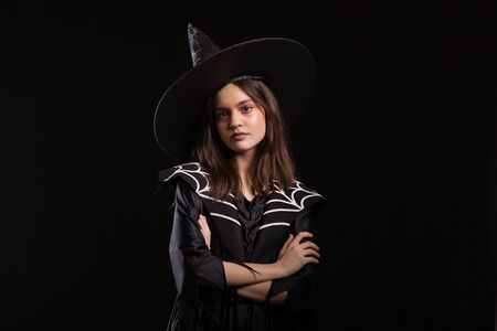 Little witch with a black dress looking at the camera with a serious expression. Young witch holding her hands crossed. Girl dressed for halloween. Reklamní fotografie