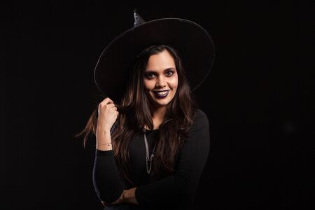 Young beautiful witch with a black dress and a big hat smiling over black background. Pretty girl ready for halloween dressed up like a witch. 免版税图像