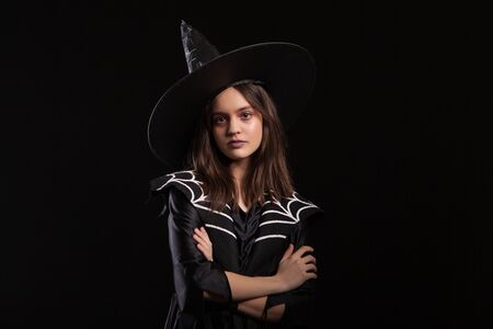 Girl doing dark spells with her arms crossed and serious expression at halloween carnival. Young witch doing dark witchcraft.