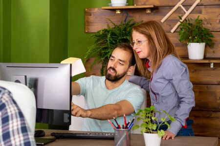 Two colleagues look to screen. . Start up company office Banque d'images - 129645262
