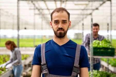 Close up pictures of a young farmer in the greenhouse. Satisfied face