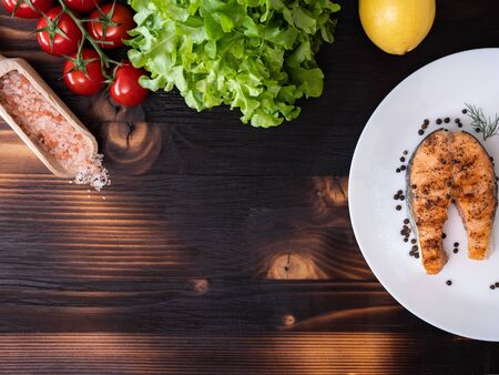 Top view of grilled salmon in a white plate over a wooden background. Salad, cherry tomatoes and lemon next to it 스톡 콘텐츠