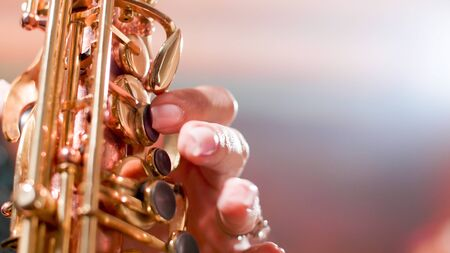 Close up of woman hands on saxophone sining jazz in a club. Musician playing jazz on saxophone.