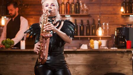 Female musician singing blues music in a blues club on her saxophone.