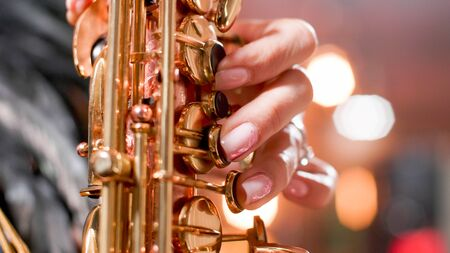 Close up hands of woman singer on a jazz concert singing on her saxophone. Woman sining jazz in club.