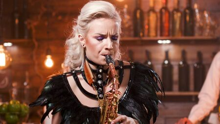 Female musician performing a jazz song on saxophone in a jazz pub. Saxophone singer.