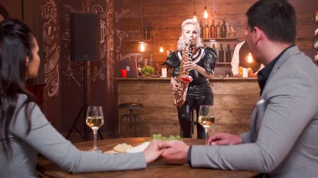 Romantic couple holding hands in a jazz pub enjoying a jazz performance on saxophone.