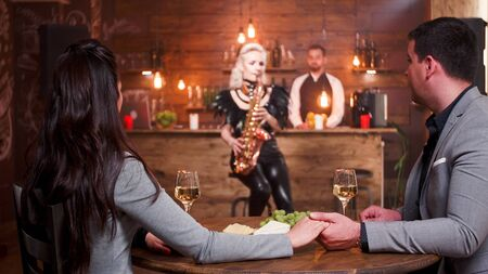 Woman in a jazz pub performing a jazz song on her saxophone for a romantic couple holding hands.