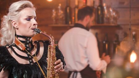 Woman singing a great song on saxophone in a club. Jazz musician.