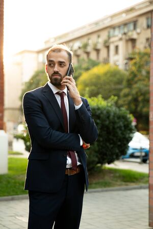 Successful businessman talking on the phone at sunset. Business style and street Stock fotó