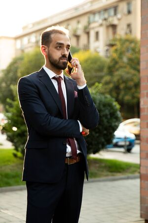 Caucasian businessman talking on the phone at sunset in the city. Business style and street view