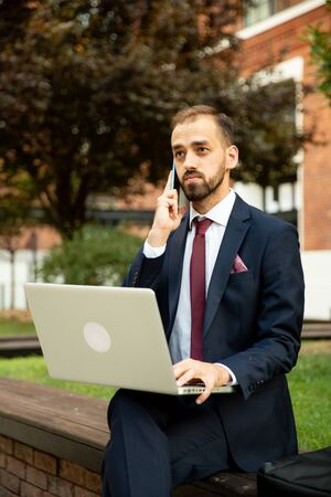 Young businessman working on laptop and talking on the phone in a green space. Suit and business attitude