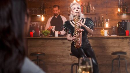 Female musician singing jazz on her saxophone in a club for a couple. Фото со стока