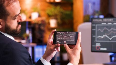 Close up as a businessman looks at some graphics on the smartphone screen. Office background