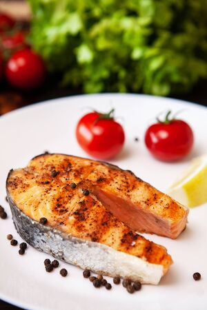 Salmon cooked on the grill arranged on a plate with tomatoes and black pepper. Lemon and salad Stock Photo