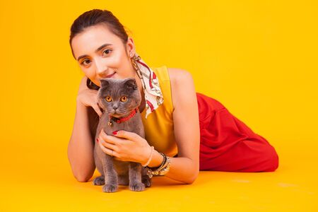 Beautiful young woman with his adorable cat in studio over yellow background.