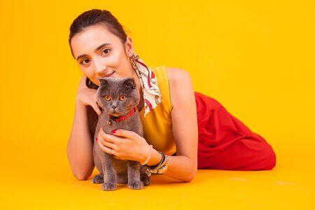 Piękna młoda kobieta z jego uroczym kotem w studio na żółtym tle.