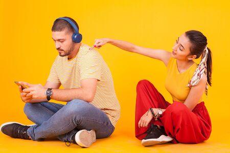 Boyfriend using her smarthphone ignoring his beautiful girlfriend. Young couple.