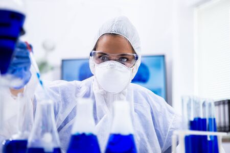Closeup view of scientist taking a sample of blue solution using a pipette from a test tube.