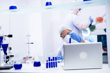 Doctor in science is analyzing a test tube in a modern lab