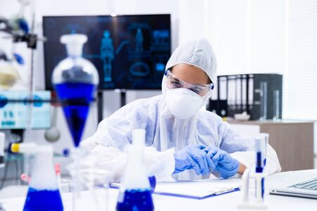 Scientist is looking at some blue specimens on the table. Pharmaceutical research