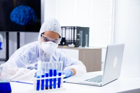 The researcher looks at a tube holder with a blue liquid in them. High-end laboratory