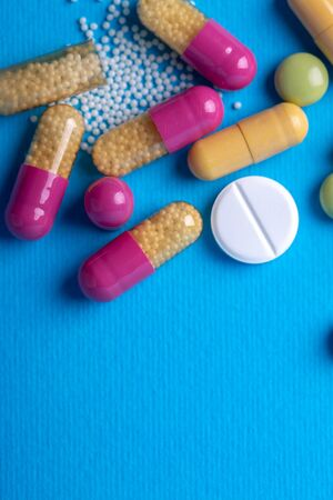 Top view with a white pill surrounded by purple and yellow capsules. Copy space and blue background