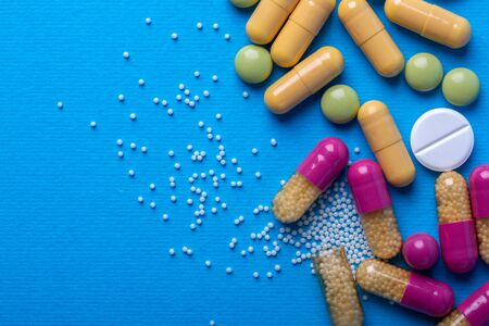 Top view with white pills and yellow capsules and purple and green pills. Copy space and macro