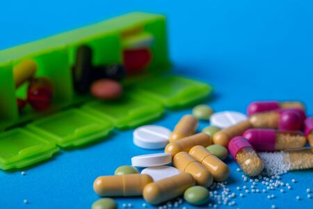 Close up with multicolored pills and capsules. Organizer in the back. Macro and blue background