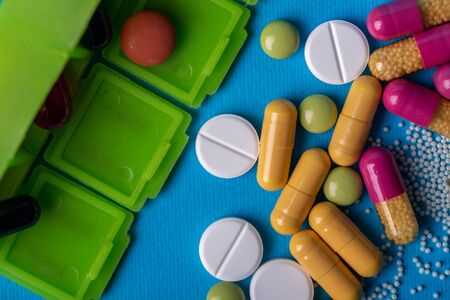 Top view with a green organizer and capsules and multicolored pills. Blue background and macro