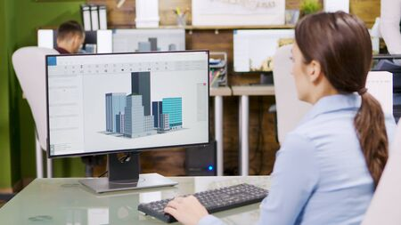 Female architect making 3d building models on computer. Architect holding blueprint. Banco de Imagens