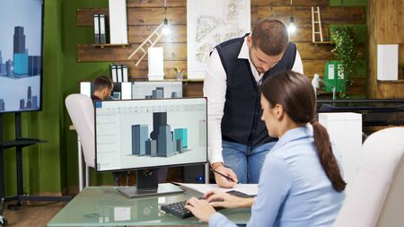 Construction engineer and female architect having a discussion about new office buildings. Architect holding building models.