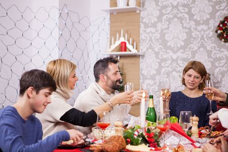Family celebrating christmas in a cozy apartment. Christmas decoration. Children sitting around the table. Banque d'images