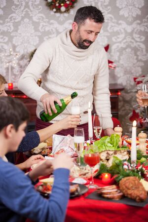 Adult man with a bottle of champagne in his hands and talking with members of the family. Chrismas feast. Man pouring champagne. Traditional christmas food.