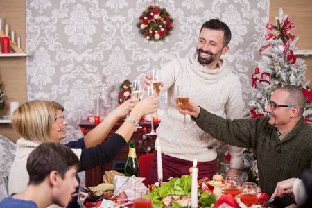 Cheerful family portrait making a toast with champagne at christmas feast. Delicious and traditional foood for christmas feast. Christmas decoration. Christmas tree. Family sitting around the table.